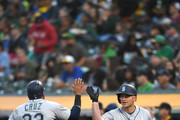 Nelson Cruz #23 of the Seattle Mariners is congratulated by Kyle Seager #15 after Cruz scored against the Oakland Athletics in the top of the third inning at Oakland Alameda Coliseum on September 1, 2018 in Oakland, California.