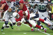 Cornerback Tre Flowers #37 and defensive back Tevon Mutcherson #38 of the Seattle Seahawks tackle running back David Johnson #31 of the Arizona Cardinals during the first quarter at State Farm Stadium on September 30, 2018 in Glendale, Arizona.