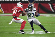 Mike Davis #27 of the Seattle Seahawks runs the ball against Antoine Bethea #41 of the Arizona Cardinals  during the first quarter at State Farm Stadium on September 30, 2018 in Glendale, Arizona.