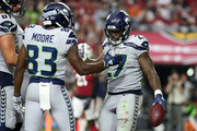 Running back Mike Davis #27 reacts with  wide receiver David Moore #83 of the Seattle Seahawks after scoring a one-yard touchdown during the third quarter against the Arizona Cardinals at State Farm Stadium on September 30, 2018 in Glendale, Arizona.