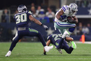 Rod Smith #45 of the Dallas Cowboys leaps over Earl Thomas #29 of the Seattle Seahawks on a carry in the second quarter of a football game at AT&T Stadium on December 24, 2017 in Arlington, Texas.