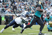 Chris Ivory #33 of the Jacksonville Jaguars runs with the football against Jarran Reed #90 of the Seattle Seahawks during the first half of their game at EverBank Field on December 10, 2017 in Jacksonville, Florida.