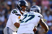 Russell Wilson #3 of the Seattle Seahawks fakes a handoff to Mike Davis #27 during a 36-31 loss to the Los Angeles Rams at Los Angeles Memorial Coliseum on November 11, 2018 in Los Angeles, California.