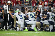 Quarterback Russell Wilson #3, Nazair Jones #92 and Duane Brown #76 of the Seattle Seahawks kneel down with teammates around defensive back Earl Thomas #29 of the Seahawks after an injury to Thomas during an NFL game against the Arizona Cardinals at State Farm Stadium on September 30, 2018 in Glendale, Arizona.