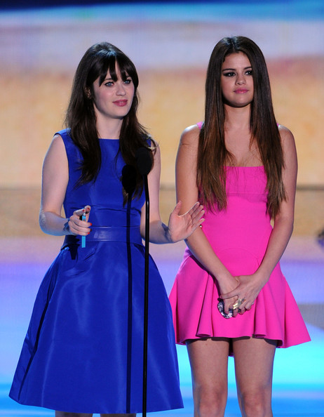 Selena Gomez Actresses Zooey Deschanel (L) and Selena Gomez speak onstage during the 2012 Teen Choice Awards at Gibson Amphitheatre on July 22, 2012 in Universal City, California.