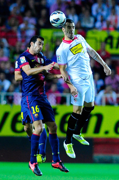 Alvaro Negredo of Sevilla FC saves on a header of Sergio Busquets of FC Barcelona during the La Liga match between Sevilla FC and FC Barcelona at Estadio Ramon Sanchez Pizjuan on September 29, 2012 in Seville, Spain.