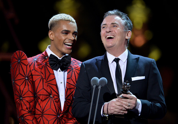 The Olivier Awards 2019 With Mastercard - Show [performance,event,formal wear,suit,music,performing arts,singing,musician,tuxedo,musical ensemble,layton williams,shane richie,olivier awards,award,stage,england,london,l,mastercard - show,the olivier awards]