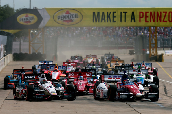 Takuma Sato (R) of Japan, driver of the #14 ABC Supply A. J. Foyt Racing Honda Dallara, and Will Power (L) of Australia, driver of the #12 Team Penske Chevrolet Dallara lead the pack at the start of the IZOD IndyCar Series Shell and Pennzoil Grand Prix Of Houston race #1 at Reliant Park on October 5, 2013 in Houston, Texas.