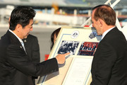 Japanese Prime Minister Shinzo Abe is presented with a framed gift prior to his departure by Australian Prime Minister Tony Abbott at Perth International Airport on July 10, 2014 in Perth, Australia. Prime Minister is in Australia for three days and will sign an Economic Partnership Agreement with Australia. Japan is Australia's second biggest trading partner.