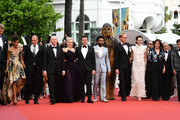 """(L-R) Joonas Suotamo, Woody Harrelson, Ron Howard, Emilia Clarke, Alden Ehrenreich, Donald Glover, Chewbacca (in costume), Paul Bettany, Phoebe Waller-Bridge, Kathleen Kennedy, Lawrence Kasdan and Jon Kasdan attends the screening of """"Solo: A Star Wars Story"""" during the 71st annual Cannes Film Festival at Palais des Festivals on May 15, 2018 in Cannes, France."""
