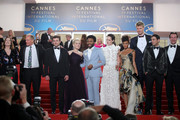 """Producer Kathleen Kennedy, actors Woody Harrelson, Alden Ehrenreich, Emilia Clarke, Donald Glover, Phoebe Waller-Bridge, Thandie Newton, Joonas Suotamo, screenwriter Jonathan Kasdan and producer Simon Emanuel depart the screening of """"Solo: A Star Wars Story"""" during the 71st annual Cannes Film Festival at Palais des Festivals on May 15, 2018 in Cannes, France."""