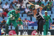 Grant Elliott of New Zealand cover drives as Mark Boucher of South Africa looks on during the ICC Champions Trophy Group B match between South Africa and New Zealand on September 24, 2009 in Centurion, South Africa.
