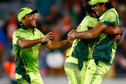 Mohammad Irfan of Pakistan (R) hugs  Wahab Riaz (C) after taking the last wicket to win the match during the 2015 ICC Cricket World Cup match between South Africa and Pakistan at Eden Park on March 7, 2015 in Auckland, New Zealand.