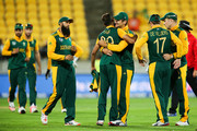 Rilee Rossouw and Imran Tahir (C) of South Africa celebrate the wicket of Shaiman Anwar of the United Arab Emirates during the 2015 ICC Cricket World Cup match between South Africa and the United Arab Emirates at Wellington Regional Stadium on March 12, 2015 in Wellington, New Zealand.