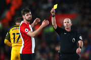 Referee Mike Dean shows a yellow card to Jack Stephens of Southampton during the Premier League match between Southampton and Brighton and Hove Albion at St Mary's Stadium on January 31, 2018 in Southampton, England.