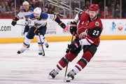 Oliver Ekman-Larsson #23 of the Arizona Coyotes skates with the puck ahead of Brayden Schenn #10 of the St. Louis Blues during the third period of the NHL game at Gila River Arena on March 31, 2018 in Glendale, Arizona.  The Coyotes defeated the Blues 5-0.