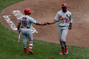 Kolten Wong #16 and Dexter Fowler #25 of the St. Louis Cardinals celebrate after Fowler scored a run in the fifth inning against the Milwaukee Brewers at Miller Park on June 24, 2018 in Milwaukee, Wisconsin.