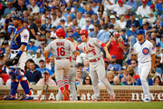 Kolten Wong #16 of the St. Louis Cardinals is congratulated by Jedd Gyorko #3 after scoring on an RBI single hit by Tommy Pham #28 (not pictured) as Willson Contreras #40 of the Chicago Cubs (L) and James Norwood #57 (R) look on during the fourth inning at Wrigley Field on July 20, 2018 in Chicago, Illinois.