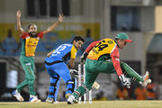 In this handout image provided by CPL T20, Imran Tahir (L) shout as Luke Ronchi (R) of Guyana Amazon Warriors attempts to catch Qais Ahmad (C) of St Lucia Stars during match 15 of the Hero Caribbean Premier League between St Lucia Stars and Guyana Amazon Warriors at the Darren Sammy Cricket Ground on August 24, 2018 in Gros Islet, Saint Lucia.