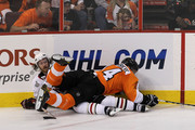 Ian Laperriere #14 of the Philadelphia Flyers falls on top of Duncan Keith #2 of the Chicago Blackhawks in Game Three of the 2010 NHL Stanley Cup Final at Wachovia Center on June 2, 2010 in Philadelphia, Pennsylvania.