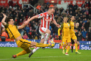 Lewis Dunk of Brighton and Hove Albion tackles Charlie Adam of Stoke City during the Premier League match between Stoke City and Brighton and Hove Albion at Bet365 Stadium on February 10, 2018 in Stoke on Trent, England.