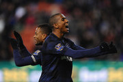 Patrice Evra of Manchester United celebrates scoring his team's second goal with team-mate Ashley Young (r) during the Capital One Cup Quarter Final match between Stoke City and Manchester United at the Britannia Stadium on December 18, 2013 in Stoke on Trent, England.