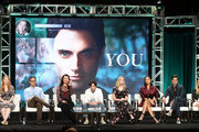 "(L-R) Sarah Schechter, Greg Berlanti, Sera Gamble, Penn Badgley, Elizabeth Lail, Shay Mitchell, John Stamos, and Caroline Kepnes of the television show ""You"" speak during the A&E segment of the Summer 2018 Television Critics Association Press Tour at the Beverly Hilton Hotel on July 26, 2018 in Beverly Hills, California."