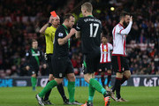 Ryan Shawcross (2nd R) of Stoke City is shown a red card by referee Mike Dean (1st L) during the Barclays Premier League match between Sunderland and Stoke City at Stadium of Light on November 28, 2015 in Sunderland, England.