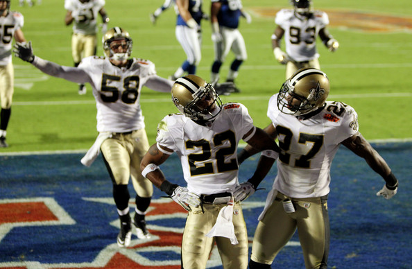 Tracy Porter #22 of the New Orleans Saints celebrates with teamates Malcolm Jenkins #27 and  Scott Shanle # 58 after retuning  a interception for touchdown against of the Indianapolis Colts during Super Bowl XLIV on February 7, 2010 at Sun Life Stadium in Miami Gardens, Florida.