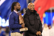 Charles Tillman (L)  wins Walter Payton NFL Player of Year trophy  prior to Super Bowl XLVIII at MetLife Stadium on February 2, 2014 in East Rutherford, New Jersey.
