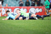 Bernard Foley of the Waratahs scores a try as he is tackled by Rob Thompson of the Highlanders during the Super Rugby Qualifying match between the Waratahs and the Highlanders at Allianz Stadium on July 21, 2018 in Sydney, Australia.