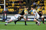 Jordie Barrett of the Hurricanes is tackled by Sam Cane and Liam Messam of the Chiefs during the round 16 Super Rugby match between the Hurricanes and the Chiefs at Westpac Stadium on June 9, 2017 in Wellington, New Zealand.