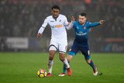 Leroy Fer of Swansea City and Aaron Ramsey of Arsenal battle for possession during the Premier League match between Swansea City and Arsenal at Liberty Stadium on January 30, 2018 in Swansea, Wales.