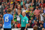 Referee Mike Dean shows Eric Dier of Tottenham Hotspur a yellow card during the Barclays Premier League match between Swansea City and Tottenham Hotspur at Emirates Stadium on October 4, 2015 in Swansea, Wales.