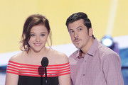 Actors Chloe Grace Moretz (L) and Christopher Mintz-Plasse speak onstage during the Teen Choice Awards 2013 at Gibson Amphitheatre on August 11, 2013 in Universal City, California.
