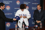 Jon Daniels (L) general manager of the Texas Rangers hands Shin-Soo Choo #17 of the Texas Rangers his cap as Choo's agent Scott Boras (R) looks on during the press conference introducing Choo to the Rangers at Rangers Ballpark in Arlington on December 27, 2013 in Arlington, Texas.