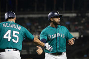 Nelson Cruz #23 of the Seattle Mariners is greeted by Kristopher Negron #45 after scoring on a single by Cameron Maybin in the second inning against the Texas Rangers at Safeco Field on September 28, 2018 in Seattle, Washington.