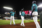 Cameron Maybin #10 of the Seattle Mariners and Guillermo Heredia #5 greet Nelson Cruz #23, right, after scoring on an error by Nomar Mazara #30 of the Texas Rangers, hit by Jean Segura, in the second inning at Safeco Field on September 28, 2018 in Seattle, Washington.