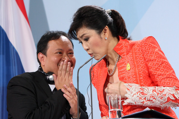Thai Prime Minister Yingluck Shinawatra (R) speaks to an aide during a