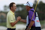 Justin Thomas (L) celebrates with his caddie Jimmy Johnson following a victory at The Honda Classic at PGA National Resort and Spa on February 25, 2018 in Palm Beach Gardens, Florida.
