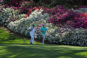 Justin Rose of England and caddie Mark Fulcher walk on the 12th hole during a practice round prior to the start of the 2018 Masters Tournament at Augusta National Golf Club on April 3, 2018 in Augusta, Georgia.
