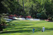 Justin Rose of England plays a shot on the 13th hole as caddie Mark Fulcher looks on during a practice round prior to the start of the 2018 Masters Tournament at Augusta National Golf Club on April 3, 2018 in Augusta, Georgia.