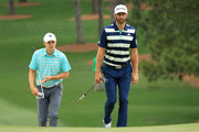 (L-R) Jordan Spieth of the United States and Dustin Johnson of the United States walk onto the seventh green during the third round of the 2018 Masters Tournament at Augusta National Golf Club on April 7, 2018 in Augusta, Georgia.