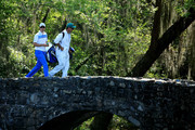 Justin Rose of England walks across the Nelson Bridge with his caddie Mark Fulcher during the third round of the 2014 Masters Tournament at Augusta National Golf Club on April 12, 2014 in Augusta, Georgia.