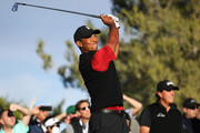 Tiger Woods plays his shot from the 13th tee as Phil Mickelson looks on during The Match: Tiger vs Phil at Shadow Creek Golf Course on November 23, 2018 in Las Vegas, Nevada.