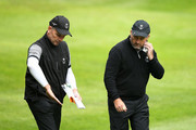 Damien McGrane of the Great Britain and Ireland PGA Cup team chats with partner David Higgins during the afternoon foursomes matches on day 2 of the 28th PGA Cup at Foxhills Golf Course on September 16, 2017 in Ottershaw, England.