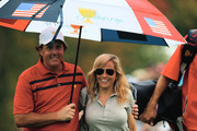 Phil Mickelson of the U.S. Team waits under an umbrella with his wife Amy during the Day Three Four-ball Matches at the Muirfield Village Golf Club on October 5, 2013  in Dublin, Ohio.