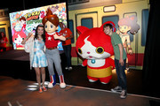 Actors Merit Leighton (L) and Benjamin Stockham  interact with costume character Jibanyan at the YO-KAI WATCH 2 preview event at Siren Studios on September 8, 2016 in Hollywood, California.