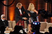"Michelle Hunziker presents a surprise dress to Thomas Gottschalk and Karl Lagerfeld made out of pictures from Gottschalks outfits during the 199th ""Wetten dass...?"" show at the Rothaus Hall on December 3, 2011 in Friedrichshafen, Germany. After 24 years host Thomas Gottschalk terminates today his career as ""Wetten dass...?"" moderator."