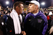 Head coach Chris Petersen (R) of the Washington Huskies shakes hands with Mike Gundy (L) of the Oklahoma State Cowboys following the TicketCity Cactus Bowl at Sun Devil Stadium on January 2, 2015 in Tempe, Arizona.  The Cowboys defeated the Huskies 30-22.